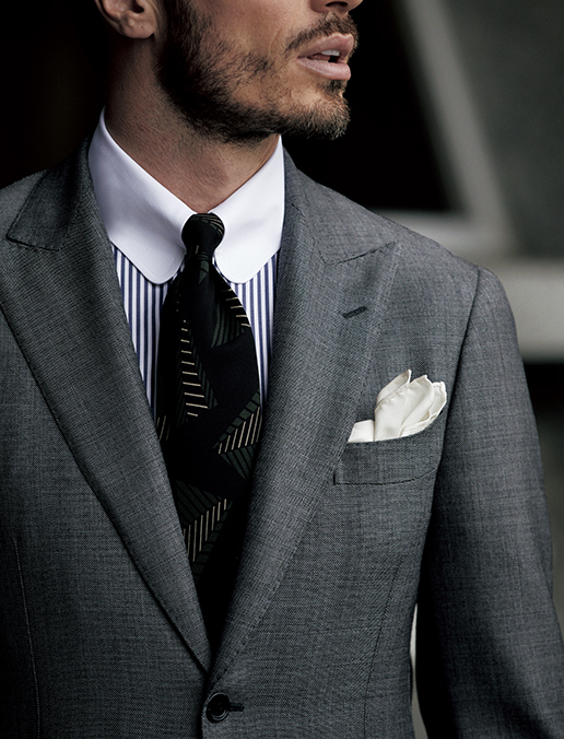 一枚毛芯でしっかり成型した胸回りとピークトラペルが、洗練された凛々しさを演出する新作スーツ。シャリ感と光沢のあるシャークスキンが美しいフォルムを一層引き立てます。ネイビーストライプのクレリックシャツや、ヴィンテージ調のブラックのプリント柄タイで、Vゾーンもシャープさを意識して。