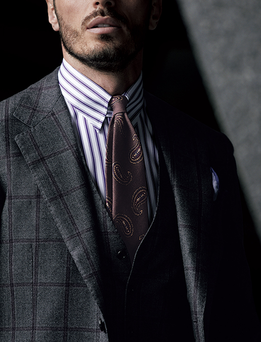 サルトリアテイストを感じさせるローゴージのクラシックなスリーピーススーツ。バルベリス社の生地は素材感豊かな表情でマッチしていますが、パープルのペーンが配されているので上品な色気が漂い、クラシックになりすぎません。さらにシャツとタイの柄色をリンクさせて品よくまとめましょう。