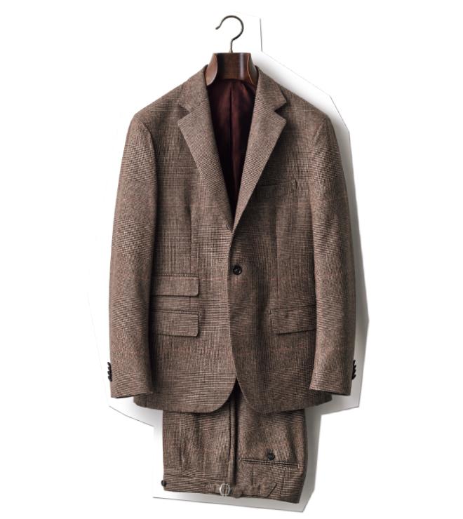 ブラウンのグレンチェック地、チェンジポケット、パンツのサイドアジャスターなど、趣味性に富んだ一着。英国的ディテールのナポリ仕立てというミックステイストのスーツです。